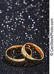 Two golden rings on black glitter background