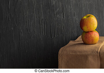 Two ripe and saturated apples on a kitchen towel