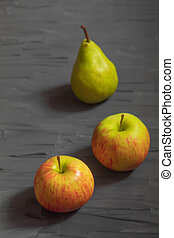 Two ripe apples and one pear on a dark gray background