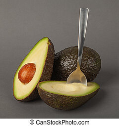 Two ripe avocado fruits lie on a gray background