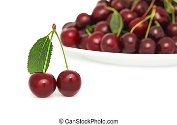Two ripe berries with green leaf and plate of cherry (isolated)