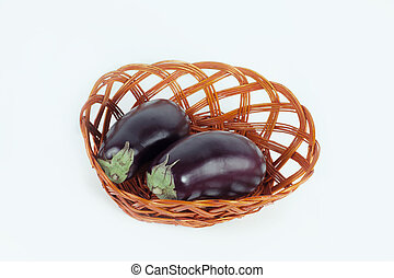 two ripe eggplant in a wicker basket. isolated on white.