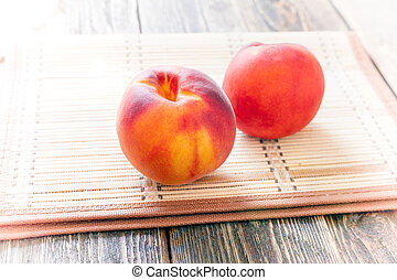 Two ripe peaches lie on a wooden table