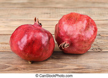 Two ripe pomegranate fruits on a wooden table.