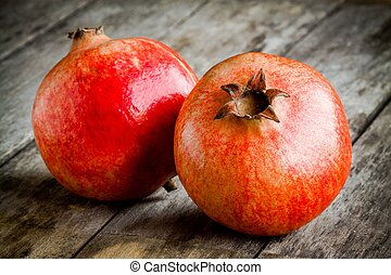 two ripe pomegranate on a wooden background