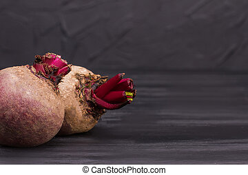 Two ripe raw beetroots on black wooden background.