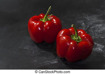 Two ripe sweet bell peppers on a black background. Close up