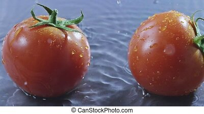 Two ripe tomatoes with water droplets. Slow motion 2k video shooted on 240 fps