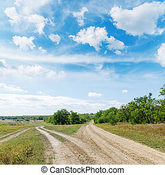two roads in green landscape under blue sky with clouds