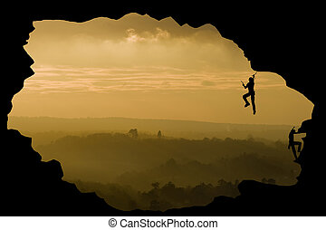 Two rock climbers silhouette against stunning sunset landscape c