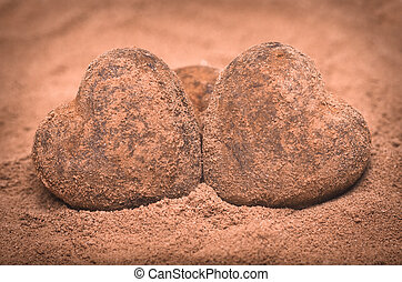 Artistic pink toned image with vignetting of two romantic heart shaped stones side by side in sand conceptual of Valentines, anniversary and love
