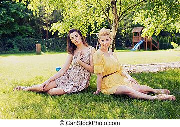 Two romantic ladies sitting on flower meadow