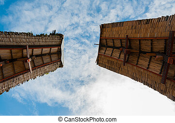 Two rooftops of traditional houses in Tana Toraja under blue cloudy sky