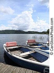 Two row boats at pier on lake