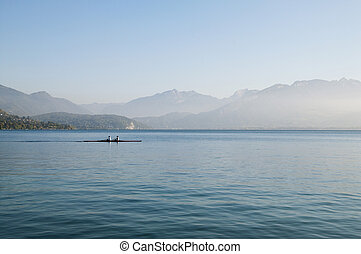Two rowers on Lake Annecy and mountains, in France.