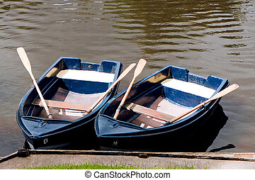 Two rowing boats with oars moored on the River Coquet