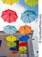 Two rows of colourful umbrellas on the sky