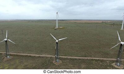 Two rows of wind energy converters whirling fans on the...