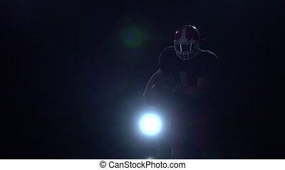 Two rugby football player go into battle face. Black background