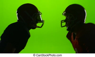 Two rugby players faced helmets in battle. Green screen. Slow motion
