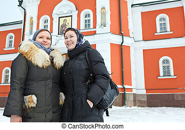 Two Russian women in winter clothes against Orthodox monastery building. Pilgrimage