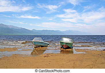 Two rusty motor boats at anchor on the beach at the shores of Lake Baikal, Russian Siberia