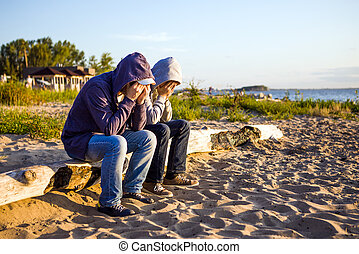 Two Sad Guys outdoor - Two Sad Men sit on the Log at the...