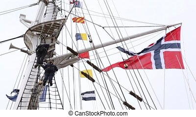 Two sailors stand above on ship mast near hanging flags