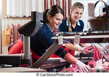Two sales ladies in butcher shop stuffing the meat display