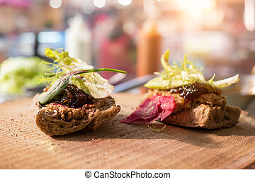 Two sandwiches on wooden board.