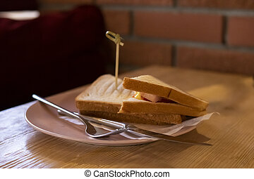 Two sandwiches with ham and tomatoes on plate on table