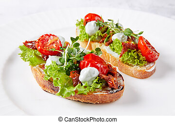 two sandwiches with vegetables on a white plate, with tomato, lettuce, herbs, mayonnaise and sauce