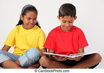 Boy and girl reading a book sitting cross legged