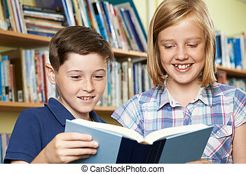 Two School Pupils Reading Book In Library