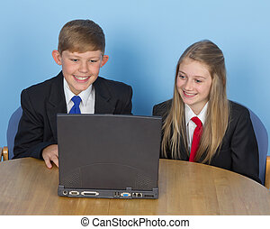 Two schoolchildren, using a computer at home