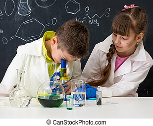 two schoolchildren watching chemical experiment