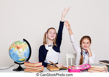 two schoolgirls girls in class at her desk with books hand to answer