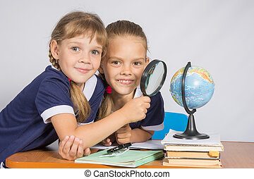 Two schoolgirls looking at globe through a magnifying glass