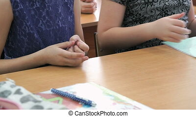 Two schoolgirls sitting at school desk restore order on school table. Close-up