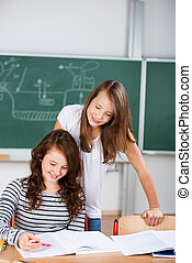 Two schoolgirls work together in a group work