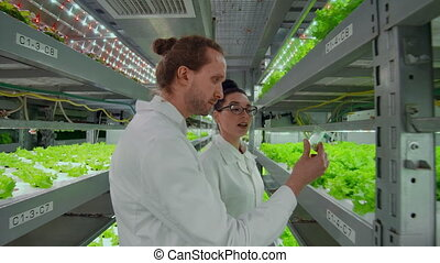 Two scientists, a man and a woman in white coats put plant...