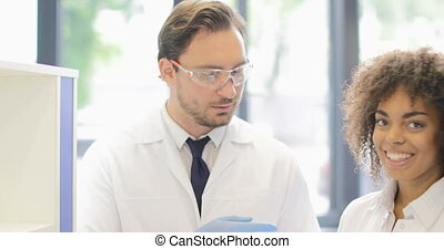 Two Scientists Discussing Documents With Result Of Experiment, Modern Researchers Team Working In Laboratory