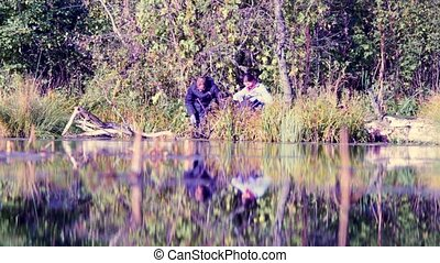 Two scientists ecologists in wild forest on the river bank....
