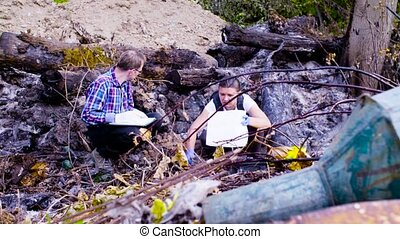 Two scientists ecologists working on place where the forest...