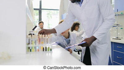 Two Scientists Examine Example In Test Tube Discuss Result Of Research Over Chemists Group Working In Laboratory