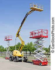 Two scissor and one articulated boom lift on asphalt ground
