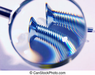two screws under a magnifying glass. a figurative picture showing a process of cheking the quality.