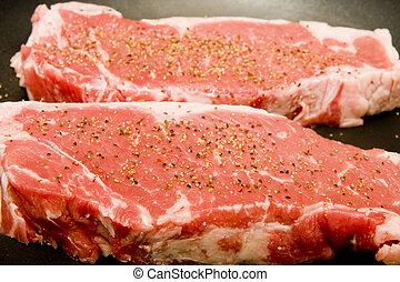 Two Seasoned Strip Steaks - Two fresh strip steaks in a...