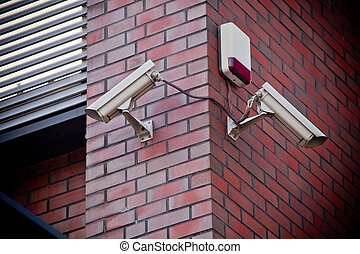 Two security cameras attached on brick wall