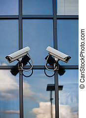 Two security cameras attached on business building with reflections